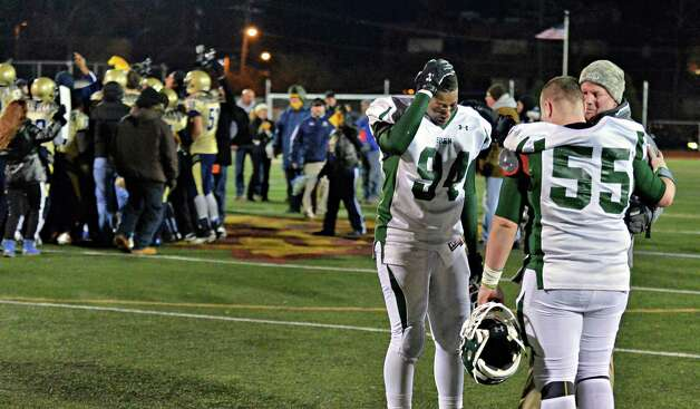 Shen line coach Mark McQuade, right, comforts #94 James Murray and #55 Dan Busold after their overtime loss to Newburgh Free Academy in the Class AA state semifinal game at Dietz Stadium Friday Nov. 22, 2014, in Kingston, NY.  (John Carl D'Annibale / Times Union) Photo: John Carl D'Annibale / 00029583A