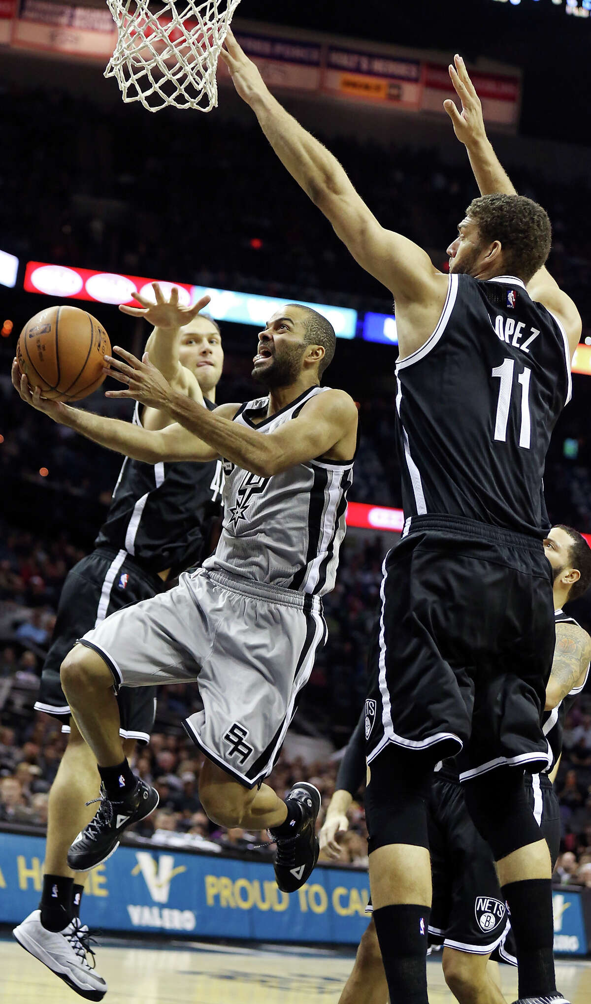 San Antonio Spurs' Tony Parker drives to the basket between Brooklyn Nets' Bojan Bogdanovic (left) and Brook Lopez during first half action Saturday Nov. 22, 2014 at the AT&T Center.