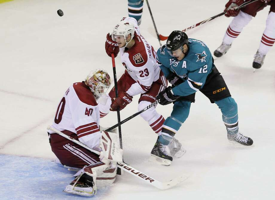 Sharks center Patrick Marleau battles for the puck against Coyotes goalie Devan Dubnyk and defenseman Oliver Ekman-Larsson during the second period. Photo: Eric Risberg / Associated Press / AP