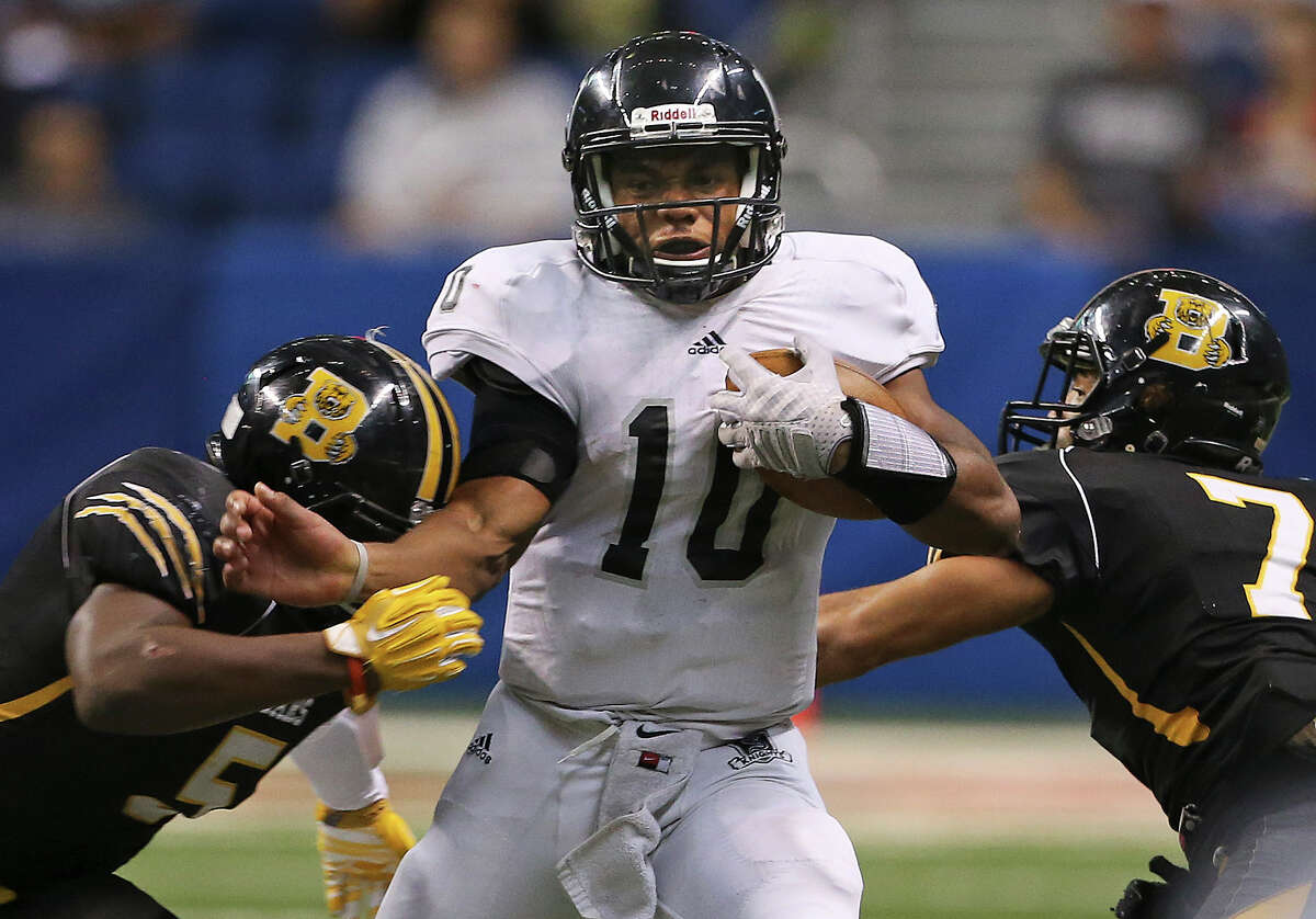 Knight quarterback LG Williams wedges his way between Dj Allen (left) and Devontre McGarity as Steele plays Brennan at the Alamodome in second round 6A high school Division I I playoff action on November 22, 2014.