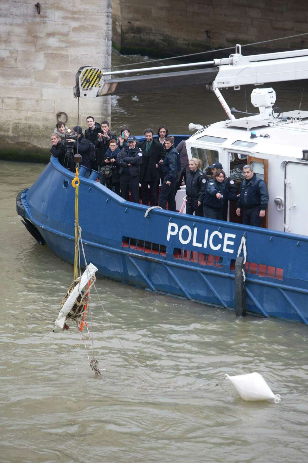 French river police lift a block of stone 2-foot-by-nearly-3-foot (60 centimeter-by-90 centimeter) from around the oldest bridge le Pont Neuf in Paris Thursday Nov. 20 2014. French authorities have found a mysterious stone sculpture at the bottom of the River Seine, which may have been there for centuries. On Thursday night, water police pulled the sculpture of a human figure with wavy hair from the depths of the river. It was discovered by a diver in September.