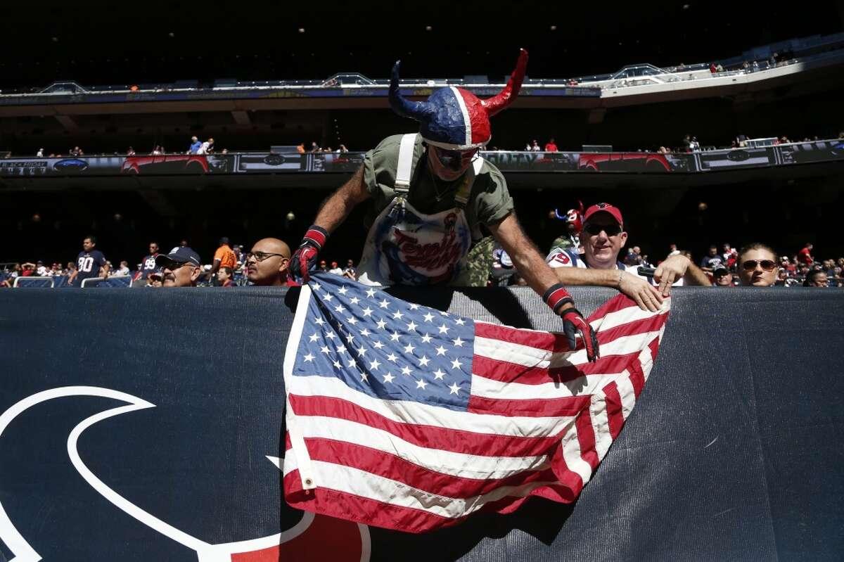 Houston Texans fan Chris Lockridge sets up an American flag before an NFL football game against the Cincinnati Bengals at NRG Stadium, Sunday, Nov. 23, 2014, in Houston. ( Karen Warren / Houston Chronicle )