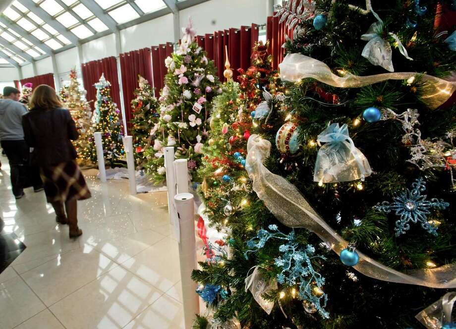 Visitors pass by decorated Christmas trees and vote on their favorites at the 12th annual Ann's Place Festival of Trees at the Matrix Conference & Banquet Center in Danbury. Sunday, Nov. 23, 2014 Photo: Scott Mullin / The News-Times Freelance