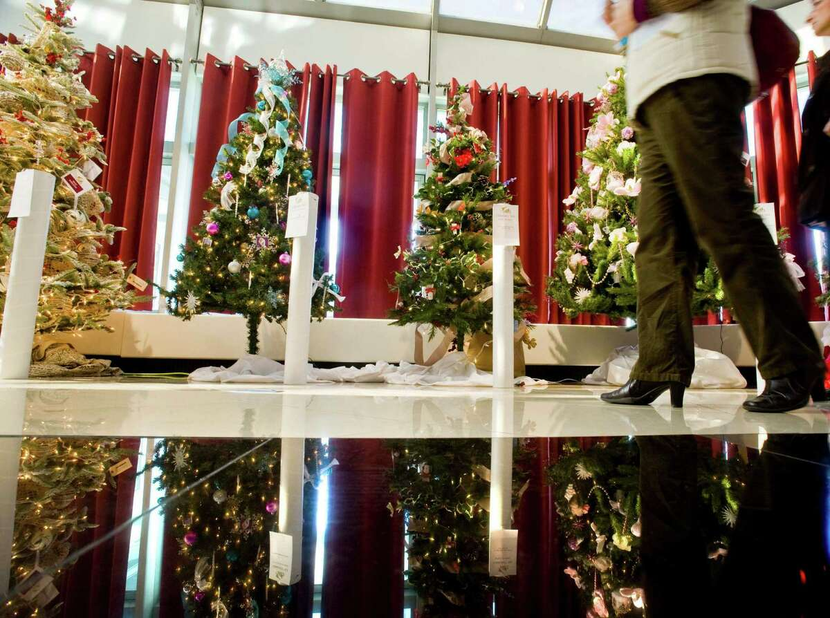 Visitors pass by decorated Christmas trees at the 12th annual Ann's Place Festival of Trees at the Matrix Conference & Banquet Center in Danbury. Sunday, Nov. 23, 2014