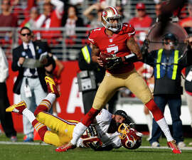 San Francisco 49ers' Colin Kaepernick scrambles as Washington's Perry Riley, Jr. loses his helmet in 1st quarter during NFL game at Levi's Stadium in Santa Clara, Calif., on Sunday, November 23, 2014.