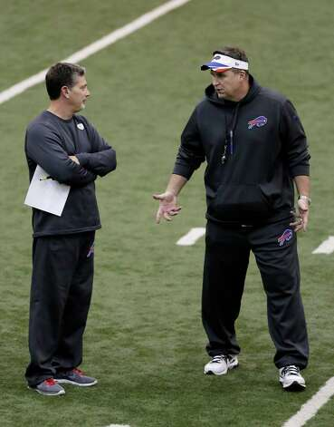 Buffalo Bills head coach Doug Marrone, right, talks with defensive coordinator Jim Schwartz during practice at the Detroit Lions' indoor NFL football training facility in Allen Park, Mich., Saturday, Nov. 22, 2014. The Bills are using the facility in preparation for Monday's game against the Jets, which was moved to Detroit because of the snowstorm in Buffalo. (AP Photo/Duane Burleson) ORG XMIT: MIDB103 Photo: Duane Burleson / FR38952 AP