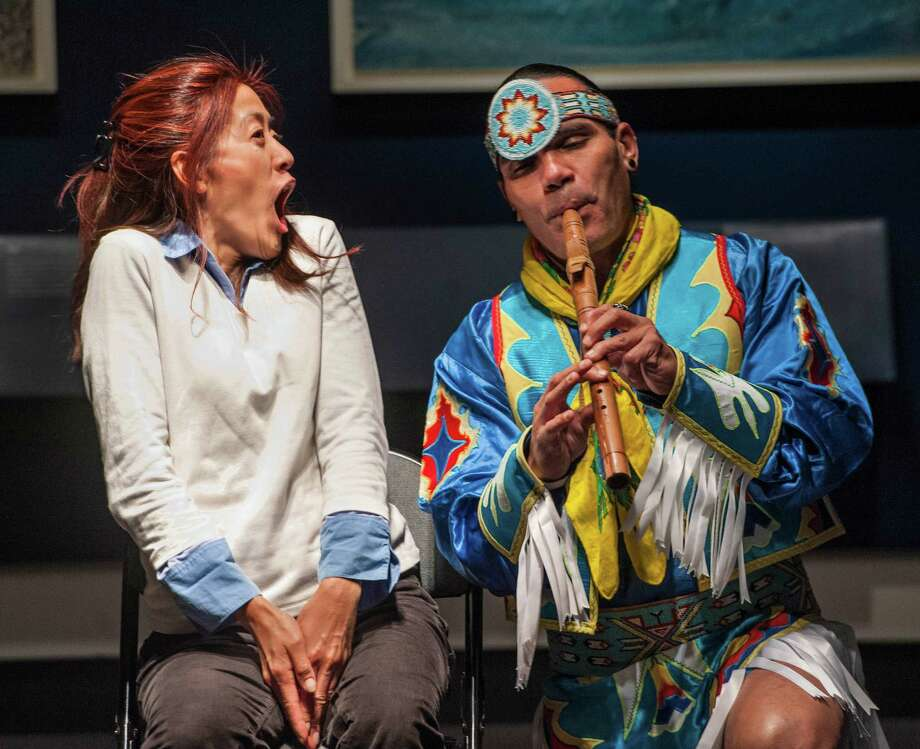"Cliff Matias of the âÄúRed Hawk DancersâÄù plays the flute to audience member Cindy Fong during the Bruce Museum Family Day dedicated to Native American traditions. The event was part of Native American Heritage month and the event included making ""Dream Catchers"" which are part of the Native American culture and a performance by the ""Red Hawk Dancers"". The event was held on Sunday, November 23rd, 2014. Photo: Mark Conrad / Connecticut Post Freelance"