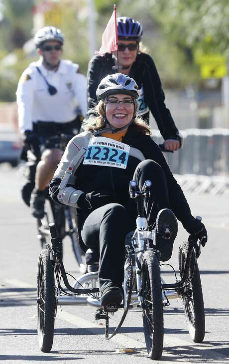 Former U.S. Rep. Gabrielle Giffords arrives back at the finish line for the 12-mile fun ride at the Special Olympics El Tour de Tucson bicycle race on Saturday, Nov. 22, 2014, in Tucson.  (AP Photo/Arizona Daily Star, Mike Christy)  ALL LOCAL TELEVISION OUT; PAC-12 OUT; MANDATORY CREDIT Photo: Mike Christy, MBR / ARIZONA DAILY STAR