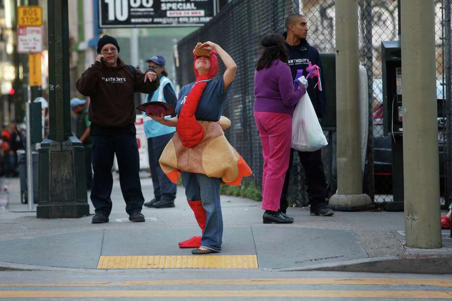 Dressed as a turkey during the first ever 4 Corner Friday, Regina Santa Maria, a social worker at St. Anthony's, holds her ground at the corner of Golden Gate Ave. and Jones Street on Friday on Nov. 14, 2014 in San Francisco, Calif. Photo: Mike Kepka / The Chronicle / ONLINE_YES