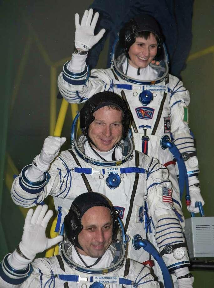 U.S. astronaut Terry Virts, center, Russian cosmo-naut Anton Shkaplerov, bottom, and Italian astro-naut Samantha Cristoforetti on their way to board the Soyuz-FG rocket for launch early Monday. Photo: Shamil Zhumatov, POOL / REUTERS POOL