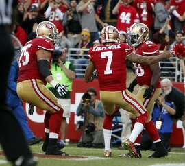 San Francisco 49ers' Carlos Hyde celebrates his 4th quarter touchdown run with Colin Kaepernick and Alex Boone during 17-13 win over Washington during NFL game at Levi's Stadium in Santa Clara, Calif., on Sunday, November 23, 2014.