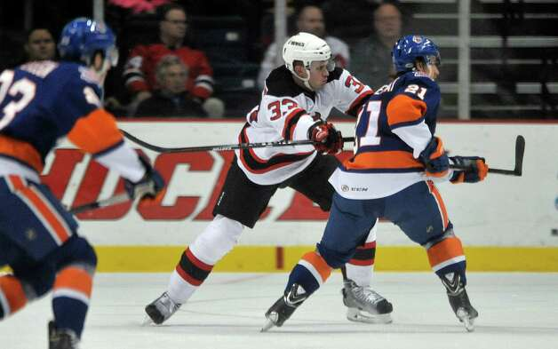 Corbin McPherson, center, with the Albany Devils defends against Kael Mouillierat during their game against the Bridgeport Sound Tigers at the Times Union Center on Sunday, Nov. 23, 2014, in Albany, N.Y.  (Paul Buckowski / Times Union) Photo: Paul Buckowski / 00029286C
