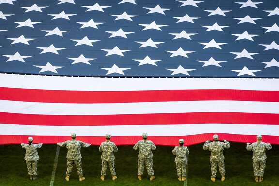 Service members hold the American flag during the national anthem before an NFL football game between the Houston Texans and the Cincinnati Bengals at NRG Stadium on Sunday, Nov. 23, 2014, in Houston. ( Smiley N. Pool / Houston Chronicle )