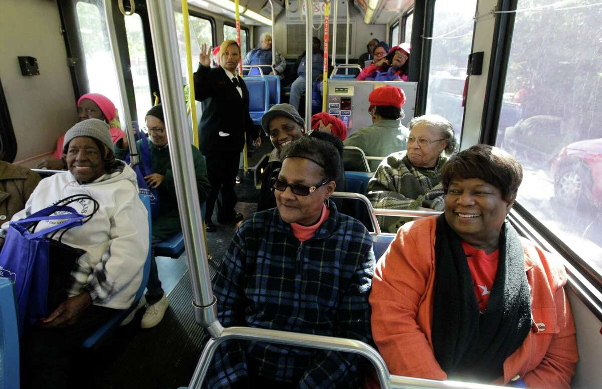 Connie Lindsey and her seat mate Bertie Chew, right, wait for others to board a bus during a METRO program at the Third Ward Community Center.