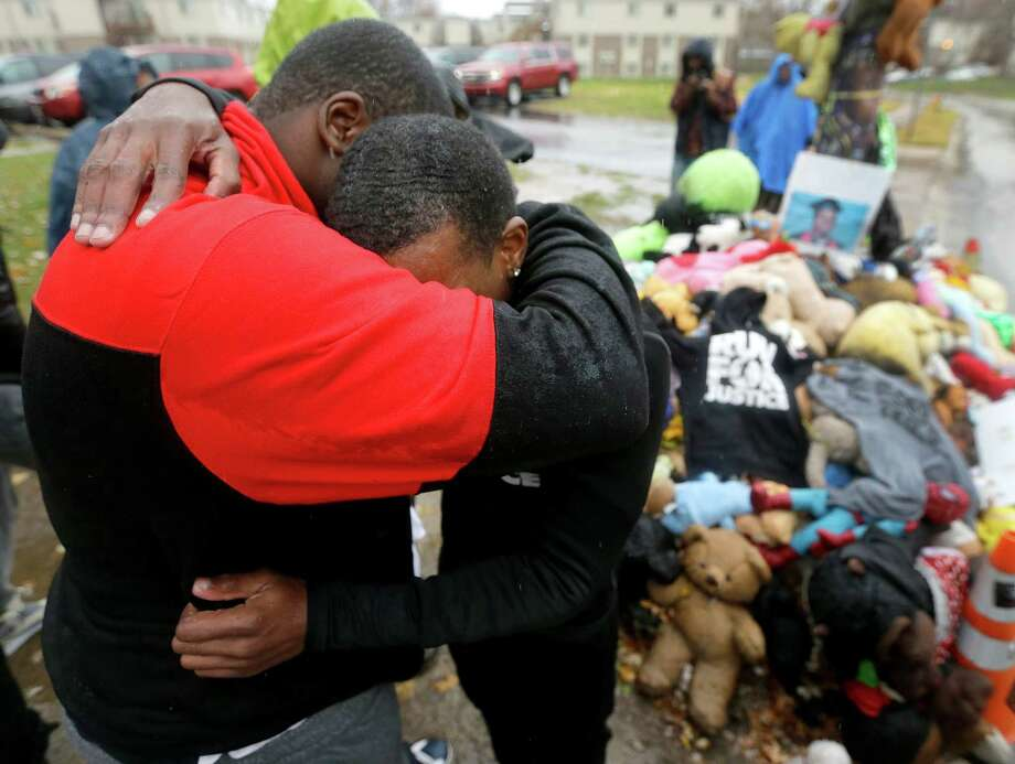 """Ferguson resident Tory Russell, left, comforts Londrelle Hall at a memorial to Michael Brown in the Missouri city Sunday.  Hall took 20 days to make a """"Run for Justice"""" from his home in Atlanta to raise awareness of the case. Photo: Charlie Riedel, STF / AP"""