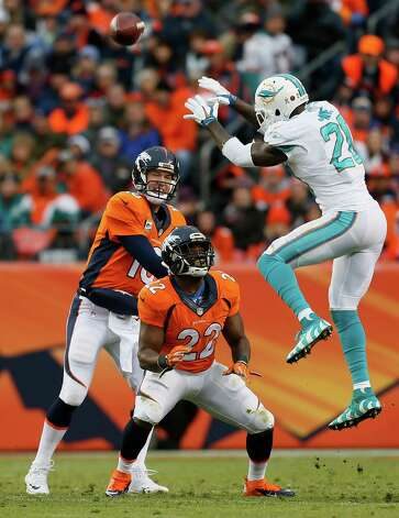 Denver Broncos quarterback Peyton Manning (18) throws as Miami Dolphins strong safety Reshad Jones (20) leaps to block during the first half of an NFL football game, Sunday, Nov. 23, 2014, in Denver. (AP Photo/Joe Mahoney)  ORG XMIT: COMY124 Photo: Joe Mahoney / FR170458 AP