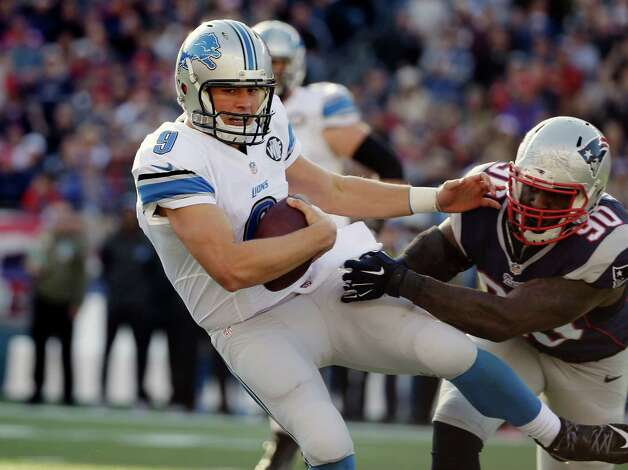 Detroit Lions quarterback Matthew Stafford (9) slips away from New England Patriots defensive end Zach Moore (90) in the first half of an NFL football game Sunday, Nov. 23, 2014, in Foxborough, Mass. (AP Photo/Steven Senne) ORG XMIT: FBO108 Photo: Steven Senne / AP