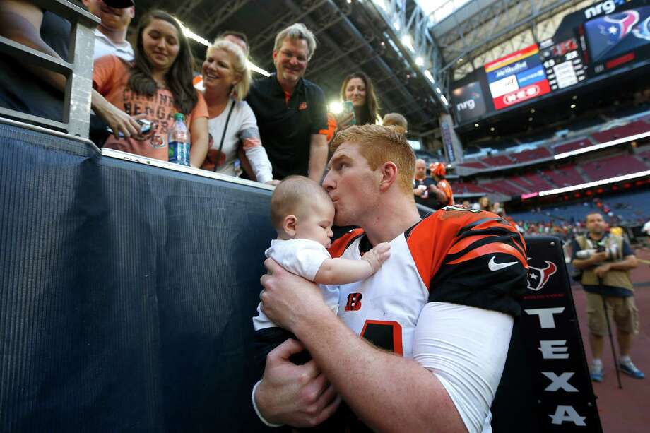 Katy native Andy Dalton celebrates finally beating the Texans with his son, Noah. Dalton gave his jersey to his father, Greg, for his birthday after the game. Photo: Brett Coomer, Staff / © 2014  Houston Chronicle