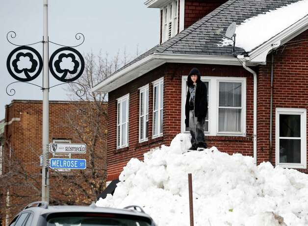 A boy stands on a snowbank in the south Buffalo area on Sunday, Nov. 23, 2014, in Buffalo, N.Y. Western New York continues to dig out from the heavy snow dropped this week by lake-effect snowstorms. (AP Photo/Mike Groll) ORG XMIT: NYMG120 Photo: Mike Groll / AP