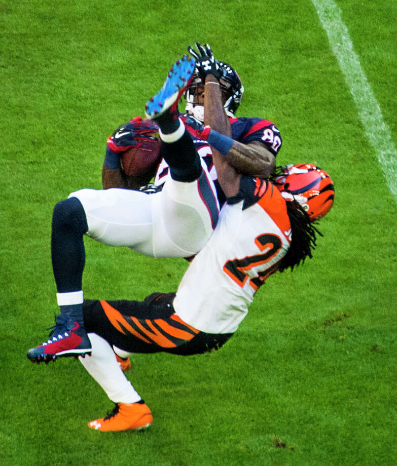 Texans wide receiver Andre Johnson (80) is brought down by Bengals cornerback Adam Jones as he makes a catch during the first quarter. Photo: Smiley N. Pool, Staff / © 2014  Houston Chronicle