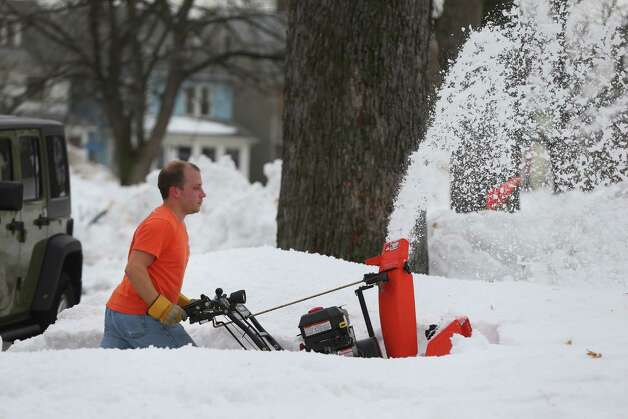 With temperatures in the high 40's John Fritz clears his neighbors driveway in a tee shirt on Oakhurst in South Buffalo Sunday, Nov. 23, 2014. (AP Photo/The Buffalo News, Mark Mulville) ORG XMIT: NYBUE104 Photo: Mark Mulville / The Buffalo News