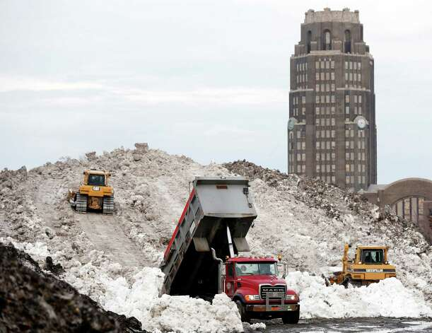A dump truck unloads snow at the Central Terminal that was removed from south Buffalo after heavy lake-effect snowstorms, Sunday, Nov. 23, 2014, in Buffalo, N.Y. Western New York continues to dig out from the heavy snow dropped this week by lake-effect snowstorms. (AP Photo/Mike Groll) ORG XMIT: NYMG122 Photo: Mike Groll / AP