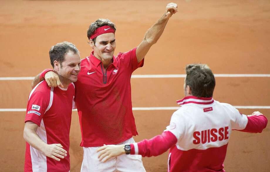 Roger Federer, center, shares the Swiss bliss with captain Severin Luthi, left, and Stanislas Wawrinka after Federer wrapped up the win over France. Photo: DENIS CHARLET, Staff / AFP