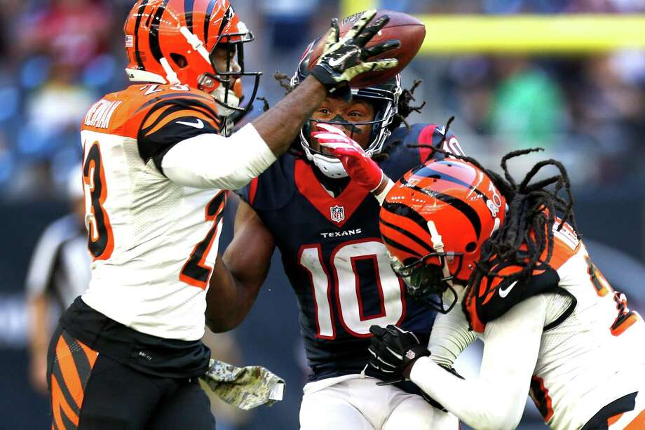 Cincinnati Bengals cornerback Terence Newman (23) and free safety Reggie Nelson (20) break up a pass intended for Houston Texans wide receiver DeAndre Hopkins (10) during the fourth quarter of an NFL football game at NRG Stadium on Sunday, Nov. 23, 2014, in Houston. ( Brett Coomer / Houston Chronicle ) Photo: Brett Coomer, Staff / © 2014  Houston Chronicle