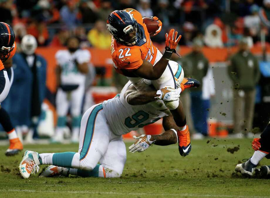 Broncos running back C.J. Anderson (22), who rushed for 167 yards, is hit by Dolphins defensive tackle Randy Starks in the second half Sunday. Photo: Jack Dempsey, FRE / FR42408 AP