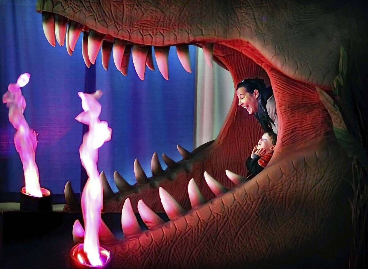 Wilson Gardeazabal, 2, and his grandmother Ingrid Gardeazabal play in the mouth of a giant Tyrannosaurus Rex at the