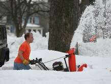 With temperatures in the high 40's John Fritz clears his neighbors driveway in a tee shirt on Oakhurst in South Buffalo Sunday, Nov. 23, 2014.