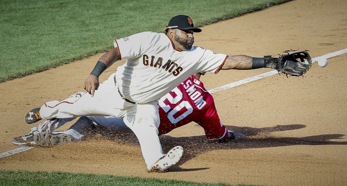 Giants Pablo Sandoval stretches for a throw from Madison Bumgarner in the seventh inning during Game 3 of the NLDS on Monday, Oct. 6, 2014 in San Francisco, Calif.