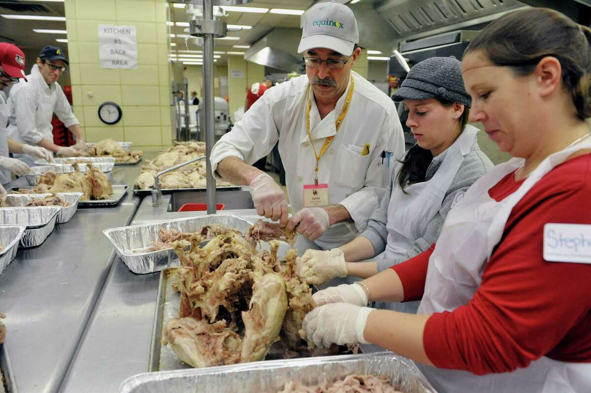Volunteer and head chef, Tom Tibbitts, left, and Alicia Beckens, center, from Schenectady and Stephanie Church from Schenectady pull turkey meat off the bones in the State kitchens at the Empire State Plaza as volunteers began preparing the food that will feed roughly 10,000 area people on Thanksgiving through the Equinox program. Tibbitts has been volunteering for the past 30 years, Beckens and Church are friends of Tom's daughter, Celia. This is the 45th year for the Annual Thanksgiving Day Community Dinner. 9,500 meals will be delivered on Thanksgiving by 800 volunteer drivers and 500 meals will be served at the sit down meal. Areas farms, Bulich Farms, Staron Farms and Denison Farms donated fresh vegetables and CDPHP donated funds as a corporate sponsor. Price Chopper donated over 12,000 pounds of turkey and Hannaford Supermarkets donated 1,200 pies. Some 3,500 volunteers will be working various day throughout the week preparing and serving the meals. (Paul Buckowski / Times Union)