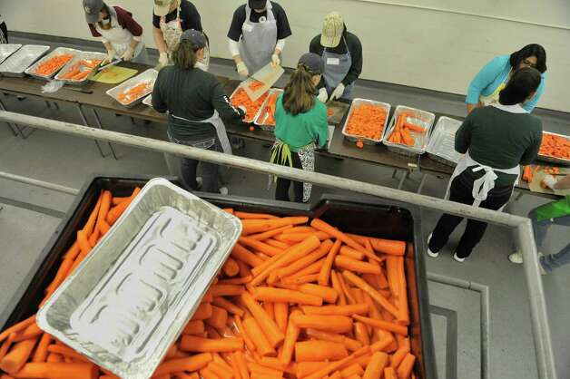 Volunteers cut up carrots in the State kitchens at the Empire State Plaza as volunteers began preparing the food that will feed roughly 10,000 area people on Thanksgiving through the Equinox program.  This is the 45th year for the Annual Thanksgiving Day Community Dinner.  9,500 meals will be delivered on Thanksgiving by 800 volunteer drivers and 500 meals will be served at the sit down meal.  Areas farms, Bulich Farms, Staron Farms and Denison Farms donated fresh vegetables and CDPHP donated funds as a corporate sponsor.  Price Chopper donated over 12,000 pounds of turkey and Hannaford Supermarkets donated 1,200 pies.  Some 3,500 volunteers will be working various day throughout the week preparing and serving the meals.  (Paul Buckowski / Times Union) Photo: Paul Buckowski / 00029584A