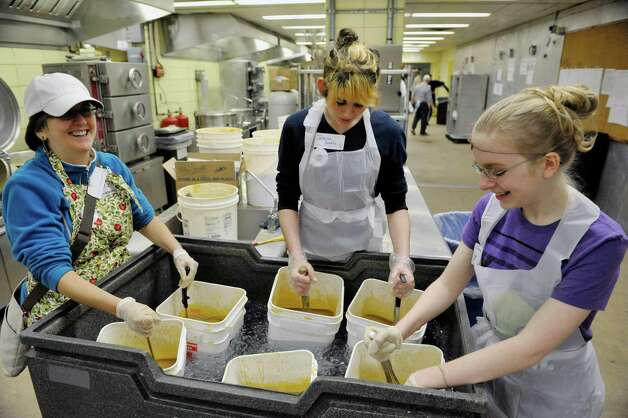 Members with the First Unitarian Universalist Society of Albany church, Kathy Macri, left, Johanna Panetta, center, and Grace Schlembach stir gravy as it cools down in an ice bath in the State kitchens at the Empire State Plaza as volunteers began preparing the food that will feed roughly 10,000 area people on Thanksgiving through the Equinox program. This is the 45th year for the Annual Thanksgiving Day Community Dinner.  9,500 meals will be delivered on Thanksgiving by 800 volunteer drivers and 500 meals will be served at the sit down meal.  Areas farms, Bulich Farms, Staron Farms and Denison Farms donated fresh vegetables and CDPHP donated funds as a corporate sponsor.  Price Chopper donated over 12,000 pounds of turkey and Hannaford Supermarkets donated 1,200 pies.  Some 3,500 volunteers will be working various day throughout the week preparing and serving the meals.  (Paul Buckowski / Times Union) Photo: Paul Buckowski / 00029584A