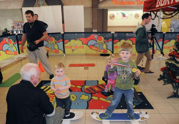 Two-year-old Anton Pitts, left, of Albany and  5-year-old Brian Bonanno,right, of Clifton Park leaern the basics during a snowboard introductory class sponsored by Jiminy Peak Mountain Resort and Bromley Mountain at Colonie Center on Saturday Nov. 22, 2014 in Colonie, N.Y. (Michael P. Farrell/Times Union) Photo: Michael P. Farrell / 00029593A