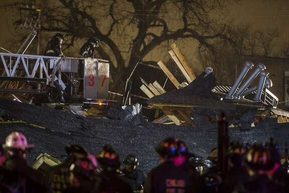 Chicago firefighters work at the scene where a house exploded and collapsed Sunday, Nov. 23, 2014 in the 5800 block of S Calumet Ave in Chicago. Two people and a dog were pulled from the rubble. (Brian Cassella/Chicago Tribune/TNS)