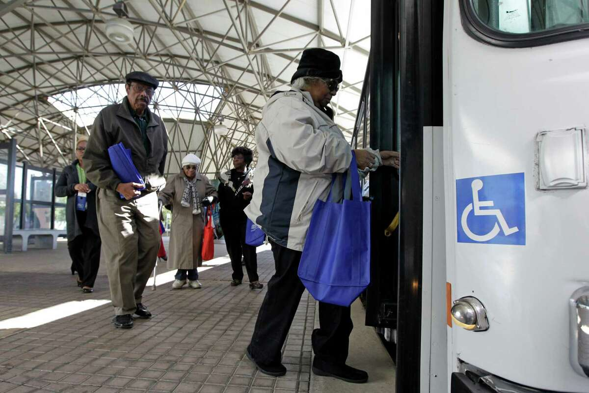 A group boards a bus at the Southeast Transit Center, which is on the 26/27 line.