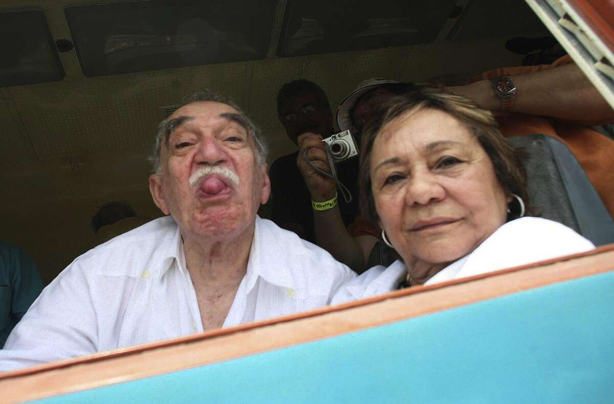 Gabriel Garcia Marquez sticks out his tongue to photographers as he arrives on a train to Aracataca, his hometown in northeastern Colombia in 2007. At right is his wife Mercedes Barcha who accompanied the writer on his first visit to his hometown in 25 years.