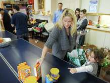 Tracy Salvatore, of Old Greenwich, and her daughter, Lyla Salvatore, 4, pack a bag of donated food at Family Centers in Greenwich, Conn. Monday, Nov. 24, 2014.  About two dozen volunteers helped pack Thanksgiving bags full of food for those in need this holiday season.  Bags were filled with donated canned food, Thanksgiving food essentials and a gift card to purchase more food with the idea that the donation could last them longer than just Thanksgiving day, but through the week.  The Family Center has been doing this for nine years now and filled well over 100 requests this year.
