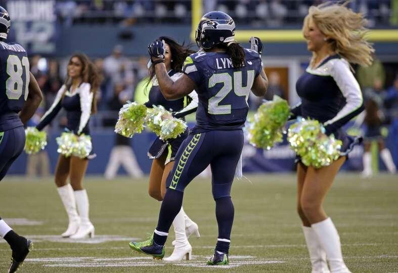 Seattle Seahawks' Marshawn Lynch (24) joins-in as Seahawks' Sea Gals cheerleaders dance on the field