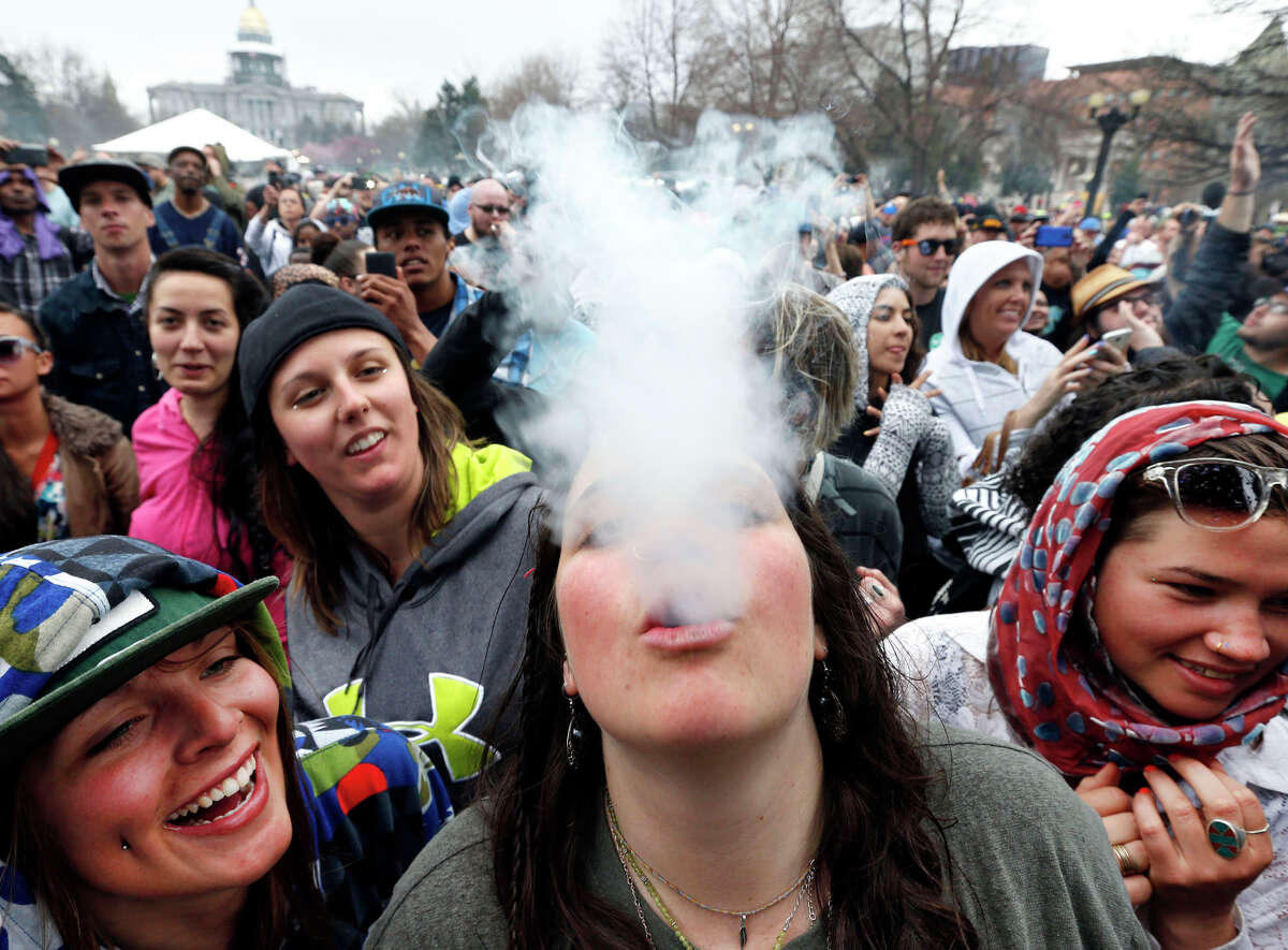 Partygoers dance and smoke pot April 19, the first of two days of the annual 4/20 marijuana festival in Denver. The 4/20 event was the first one since Colorado legalized recreational marijuana in January.