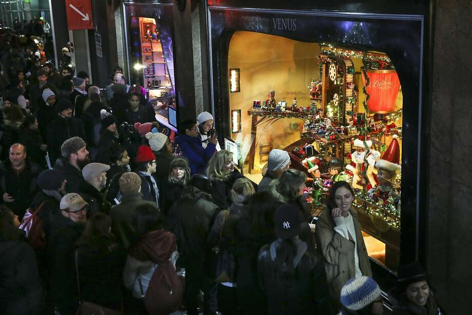 """Shoppers browse the newly unveiled 2014 Holiday Windows at the Macy's Herald Square store, on Nov. 20 in New York. This years theme is """"Santa's Journey to the Stars."""" Photo: John Minchillo, Associated Press"""