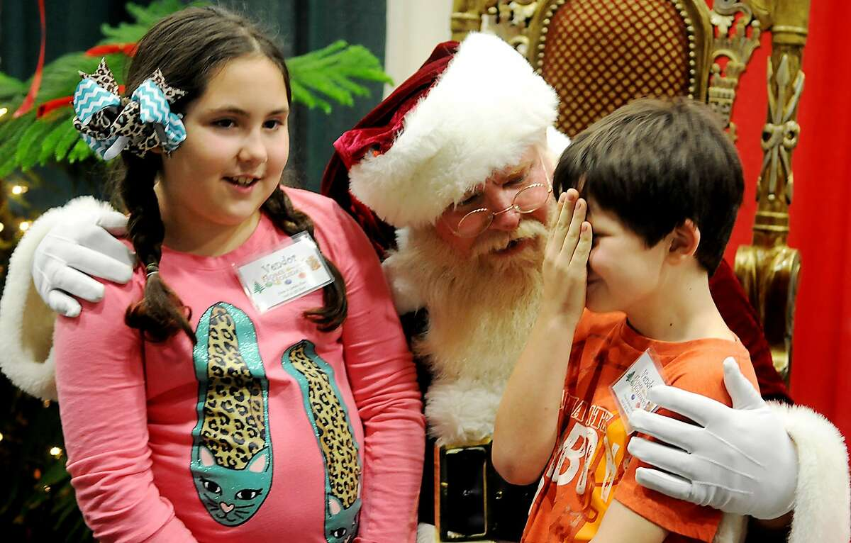 YOU BETTER NOT POUT, YOU BETTER NOT CRY. YOU BETTER NOT SUPERGLUE YOUR HAND TO YOUR NOSE: Evan Lyons is too bashful to look Santa in the eye at the Home for the Holidays show at the Chisholm Trail Expo Center in Enid, Okla. At left is his twin sister, Ripley.