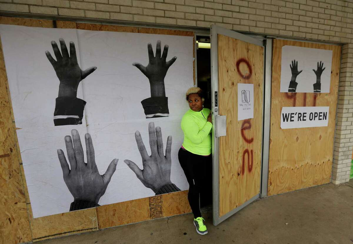 Dellena Jones looks out from her boarded-up beauty salon in the neighborhood where there was much unrest following the August shooting of of the unarmed 18-year-old Michael Brown by a police officer, Monday, Nov. 24, 2014, in Ferguson, Mo. Ferguson and the St. Louis region are on edge in anticipation of the announcement by a grand jury whether to criminally charge Officer Darren Wilson in the killing of Michael Brown. (AP Photo/Charlie Riedel)