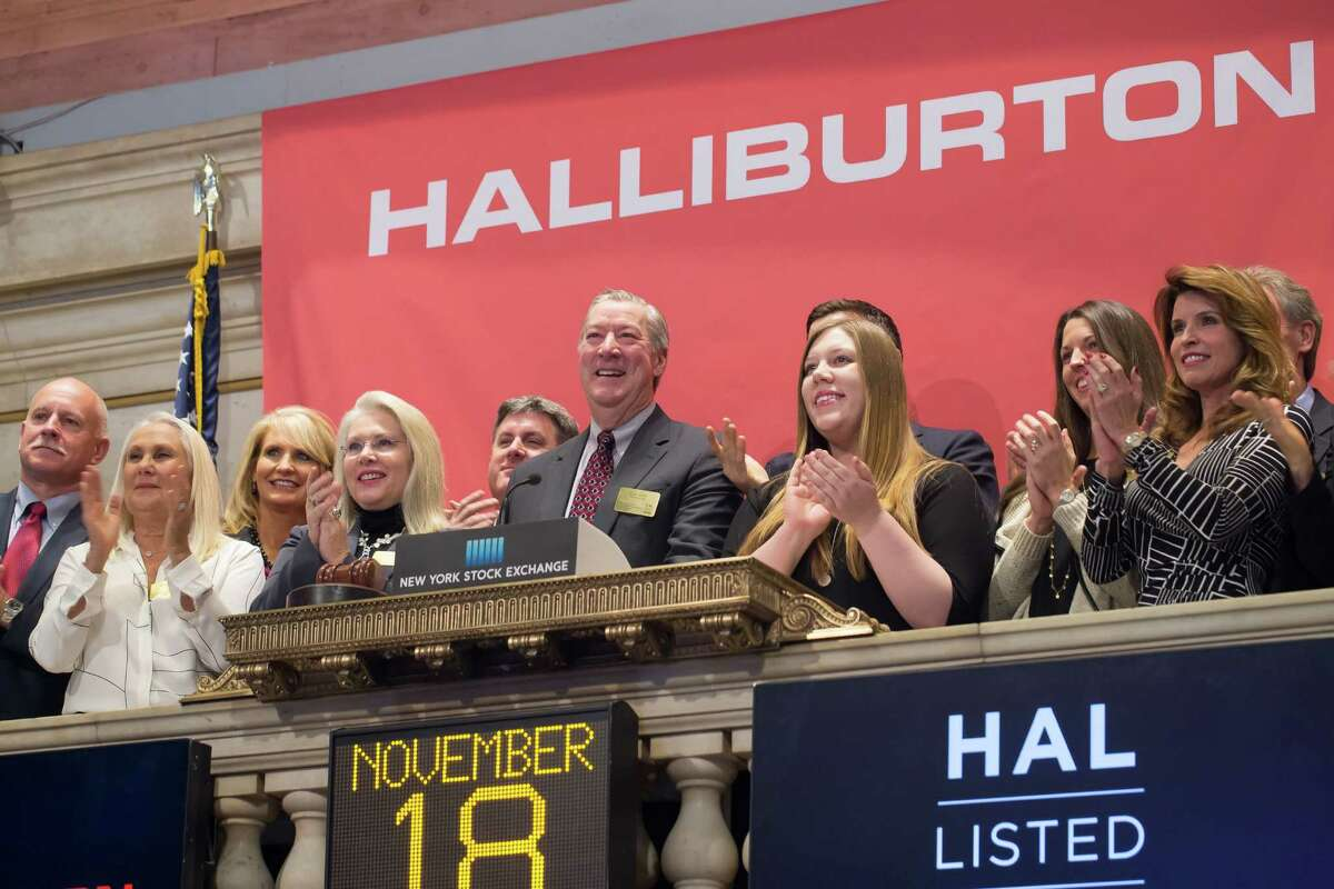 Halliburton CEO Dave Lesar, surrounded by Halliburton employees and their families, rings the opening bell on the New York Stock Exchange on Nov. 18, a day after Halliburton announced a deal to acquire oil-field services rival Baker Hughes.