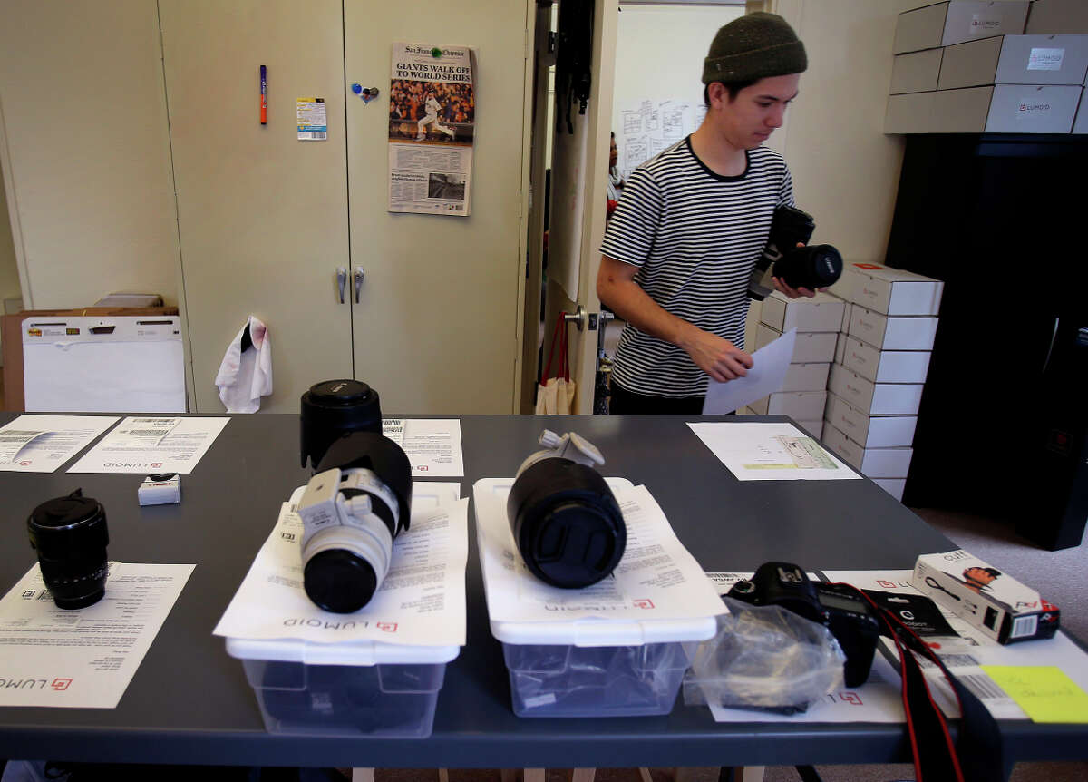 Lenses and cameras sit on a table ready to be shipped to consumers.