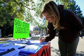 UC Berkeley student Allie Lalor signs a petition before joining in a walk-out of classes, protesting a recent approval of UC tuition hikes, on Nov. 24 at UC Berkeley.