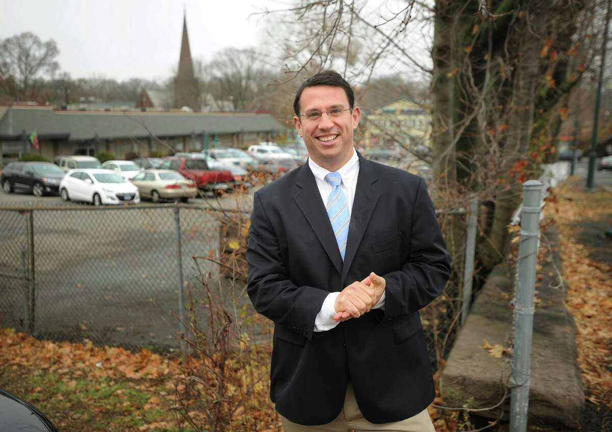Milford Mayor Ben Blake stands by one of several adjoining properties the city hopes to purchase to increase parking for the train station and downtown retailers on Monday, November 24, 2014.