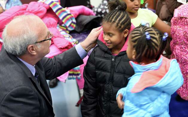 Soleil Caldwell, center, and Tiana Davis, right of Arbor Hill Elementary School are fitted for a new winter coat by Jack Yonally, president of Lodge's Department Store, left during the press conference announcing the results of the Cash for Coats program in Albany, N.Y.     (Skip Dickstein/Times Union) Photo: SKIP DICKSTEIN / 00029576A